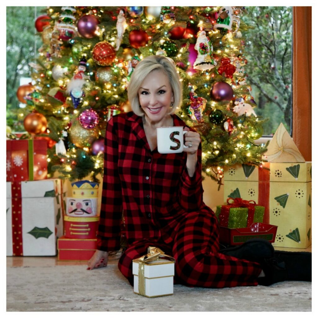 Sheree Frede of the SheShe Show sitting in front of Christmas tree holding a coffee mug, wearing red and black plaid pajamas