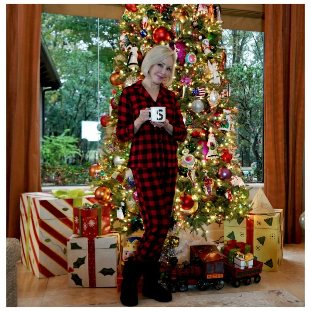 Sheree Frede of the SheShe Show standing in front of Christmas tree holding a coffee mug, wearing red and black plaid pajamas