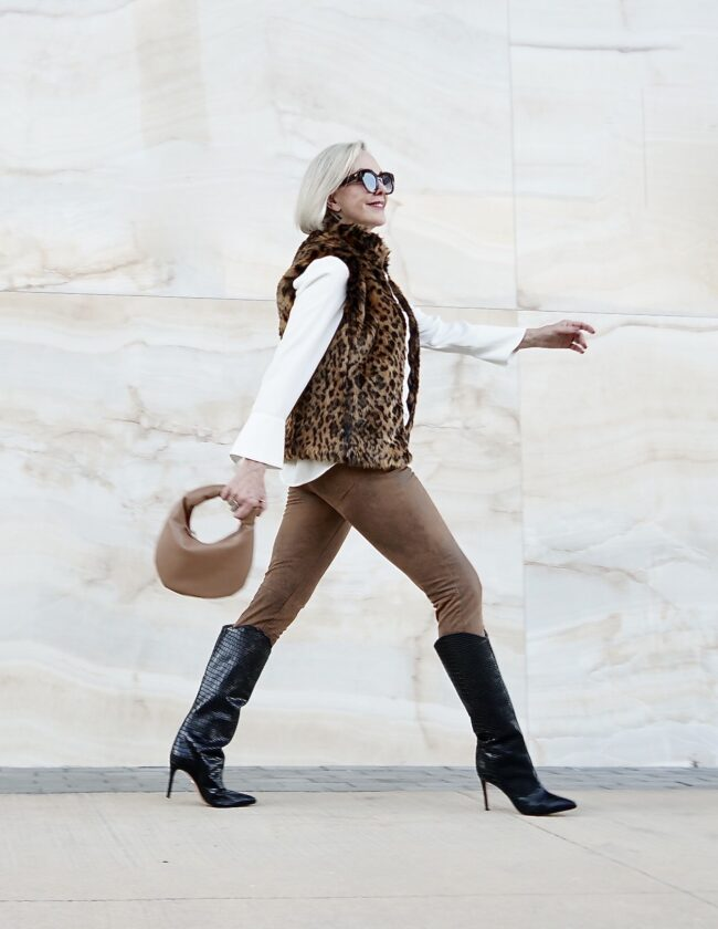 Sheree Frede of the SheShe Show walking in front of white marble wall wearing knee high heeled boots and faux fur vest