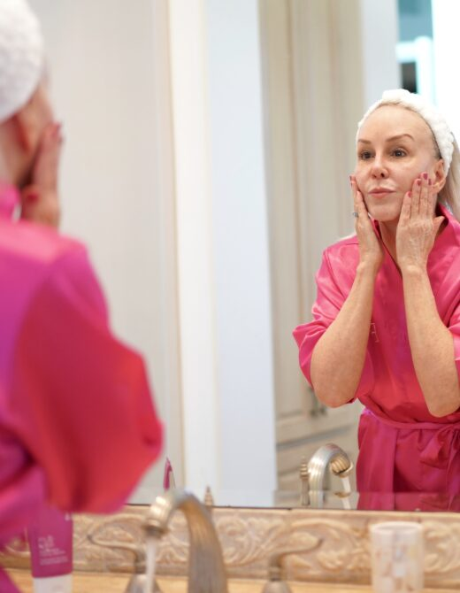Sheree frede in pink robe applying face cream