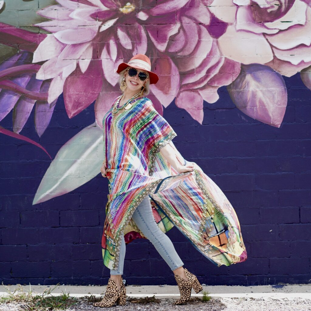 Sheree Frede of the SheShe Show walking in front of floral art wall wearing a multi colored strip kaftan and hat
