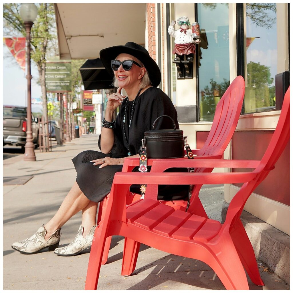 Sheree Frede of the SheShe SHow wearing a black dress sitting in a read chair on a sidewalk