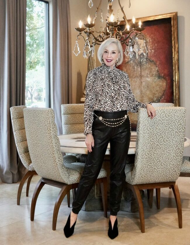 sheree frede of sheshe show in dining room wearing leather joggers and leopard blouse