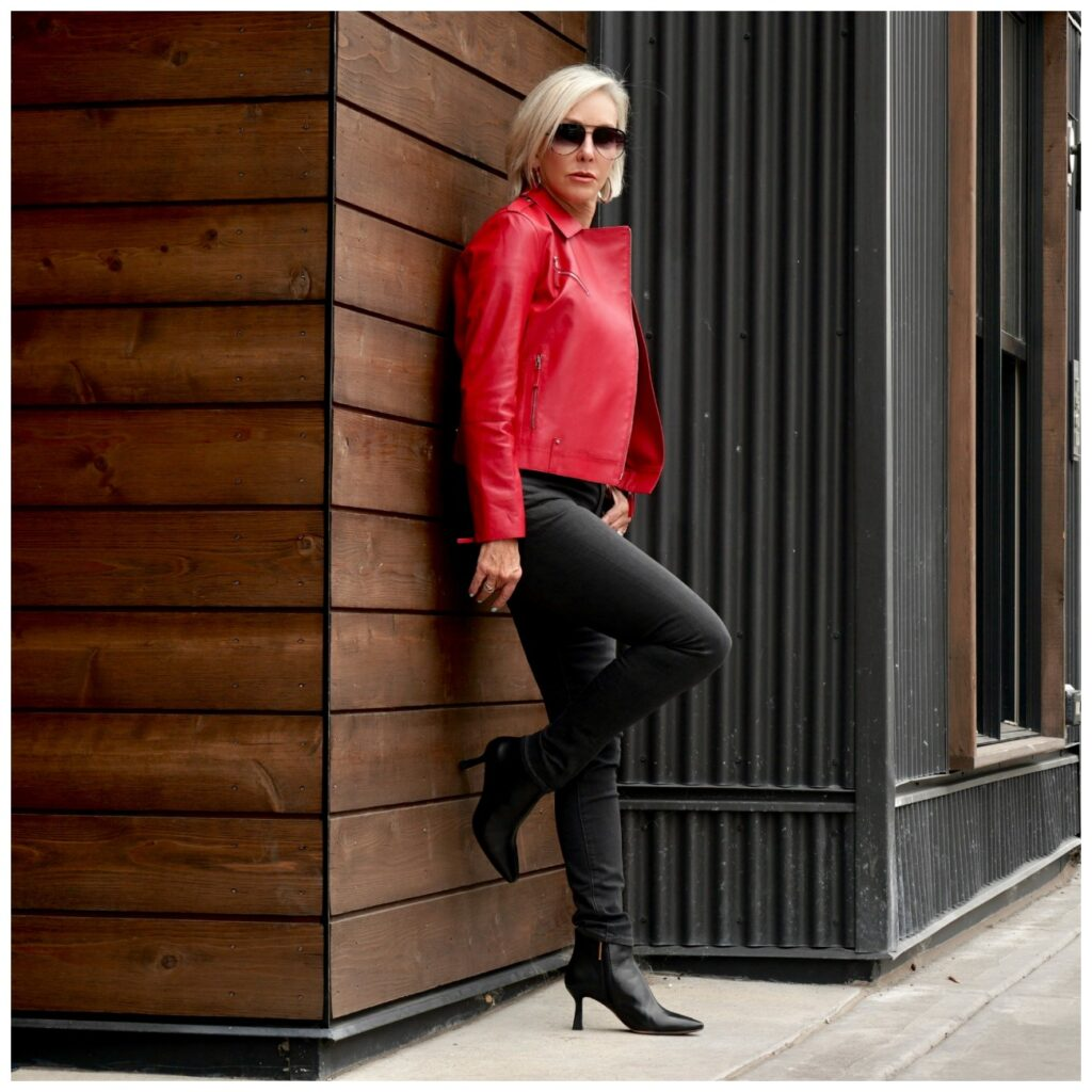 Sheree Frede of the SheShe Show standing against a brown wood wall wearing dark gray jeans and red leather moto jacket