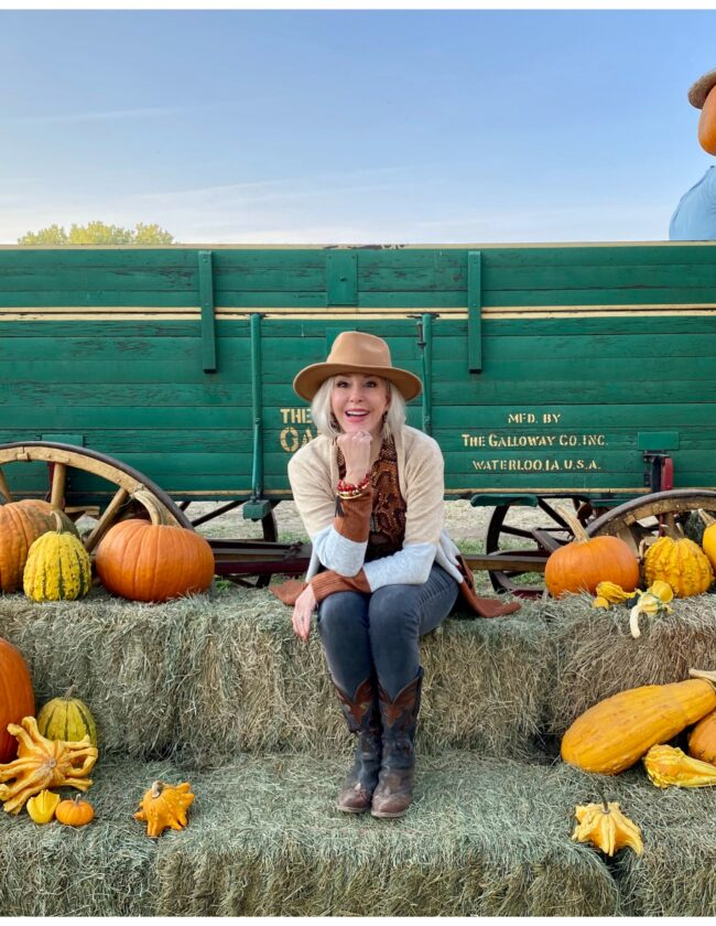 Sheree Frede of the SheShe Show sitting on a bale of hay by an old wagon wearing jeans, boots, hat and long cardigan