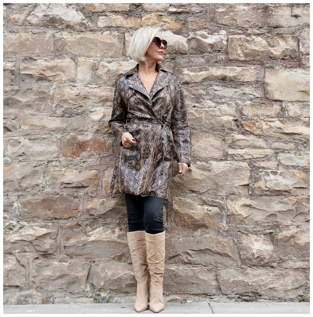 Sheree Frede of the SheShe SHow standing in front of a stone wall wearing a snakeskin print trench coat