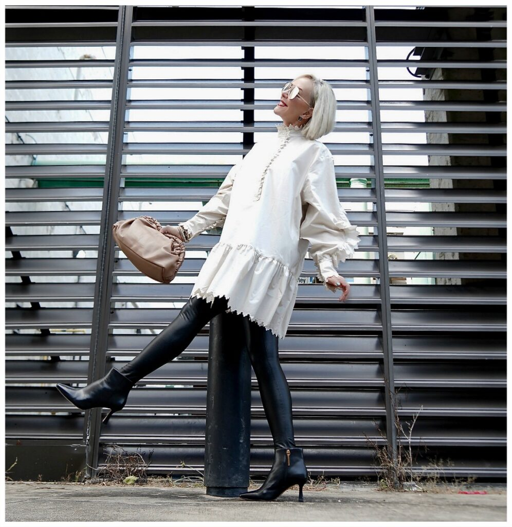Sheree Frede of the SheShe Show standing in front of metal wall wearing faux leather leggings and off white tunic top