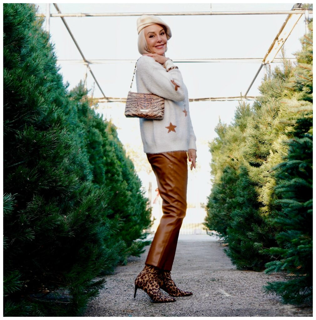 Sheree Frede of the SheShe Show standing in the Christmas tree lot wearing brown leather pants and white star sweater