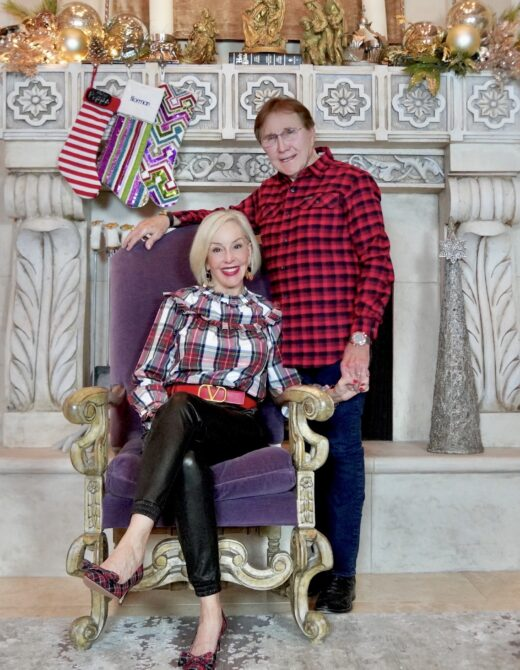 Sheree and Norman Frede in front of fireplace wearing holiday plaid