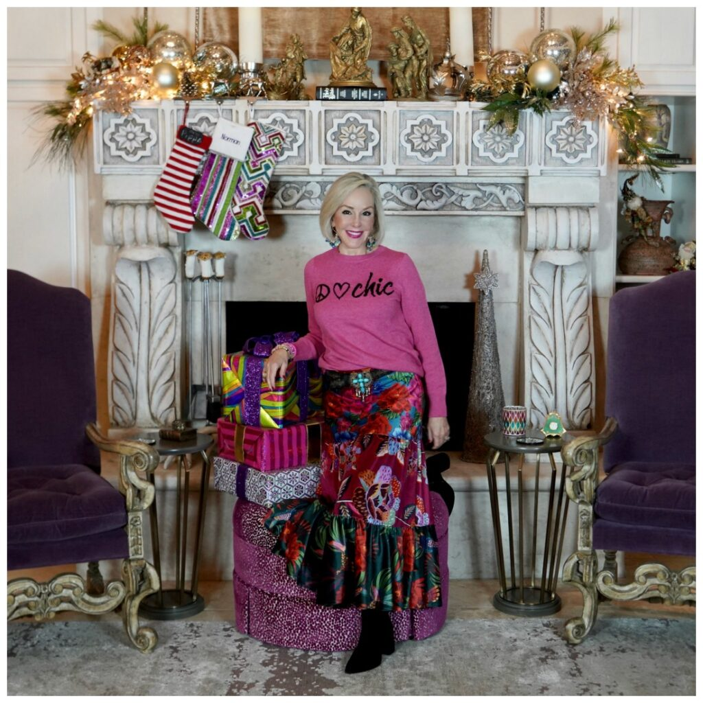 Sheree Frede of the SheShe Show standing in front of fireplace wearing a bright pink sweater and floral skirt