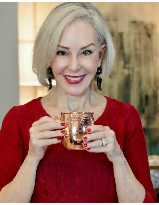 Sheree Frede of the SheShe SHow holding a copper cup wearing a red dress