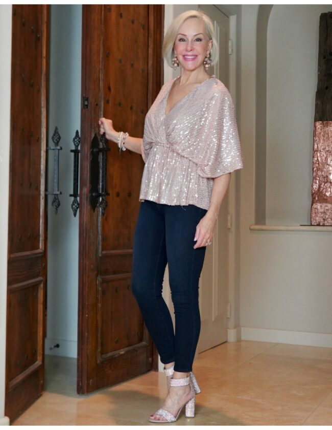 Sheree Frede of the SheShe Show standing in front of double doors wearing a blush colored sequin top and blue jeans