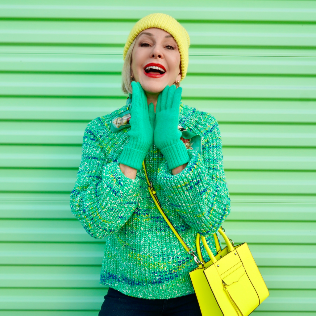Sheree Frede of the SheShe Show standing in front of green door wearing a green sweater and chartreuse beanie