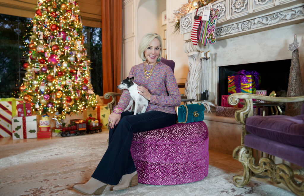 Sheree Frede of the SheShe Show sitting on an ottoman holding her white Toy Fox Terrier doggie