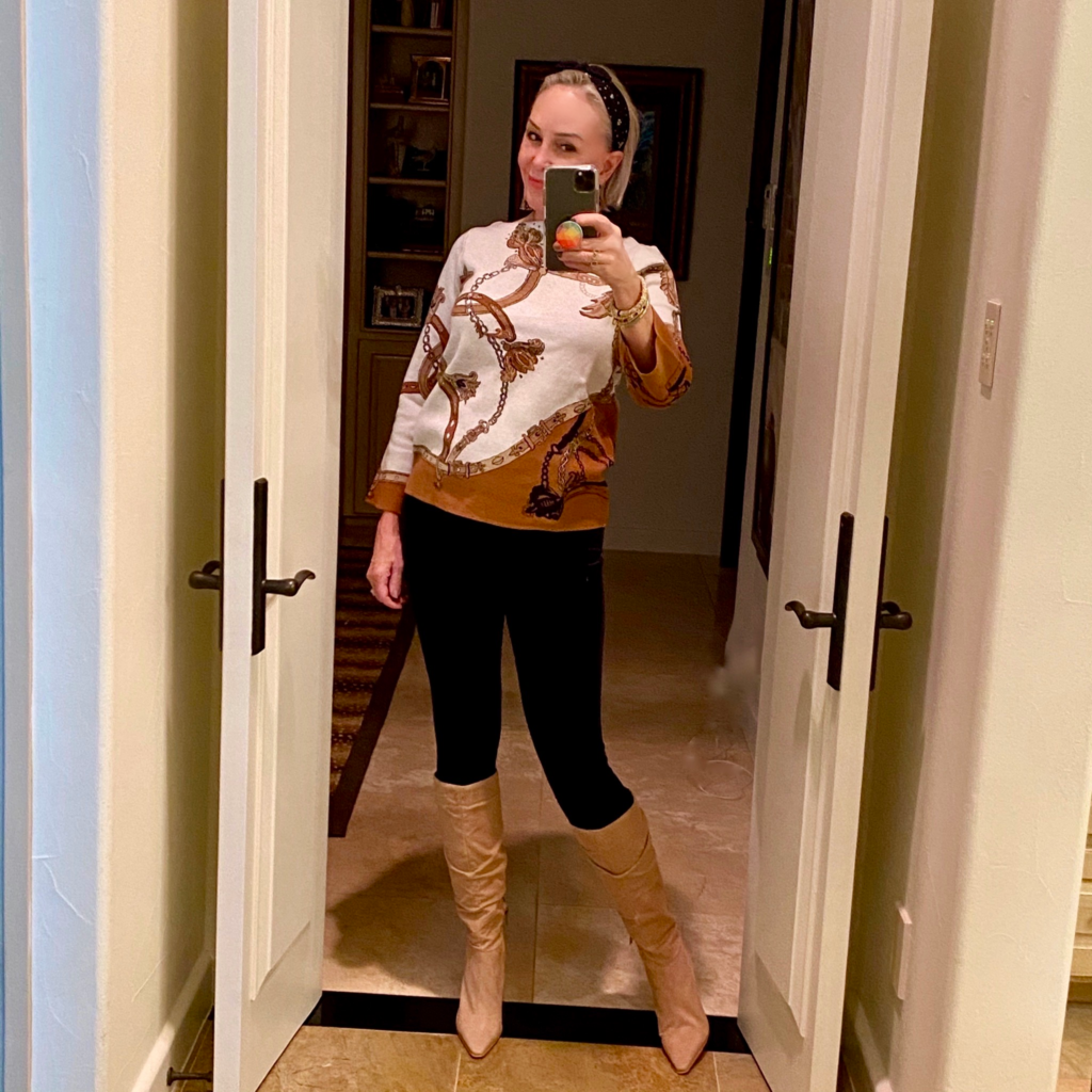 Sheree Frede of the SheShe Show standing in front of mirror wearing an equestrian print sweater over leggings and knee boots