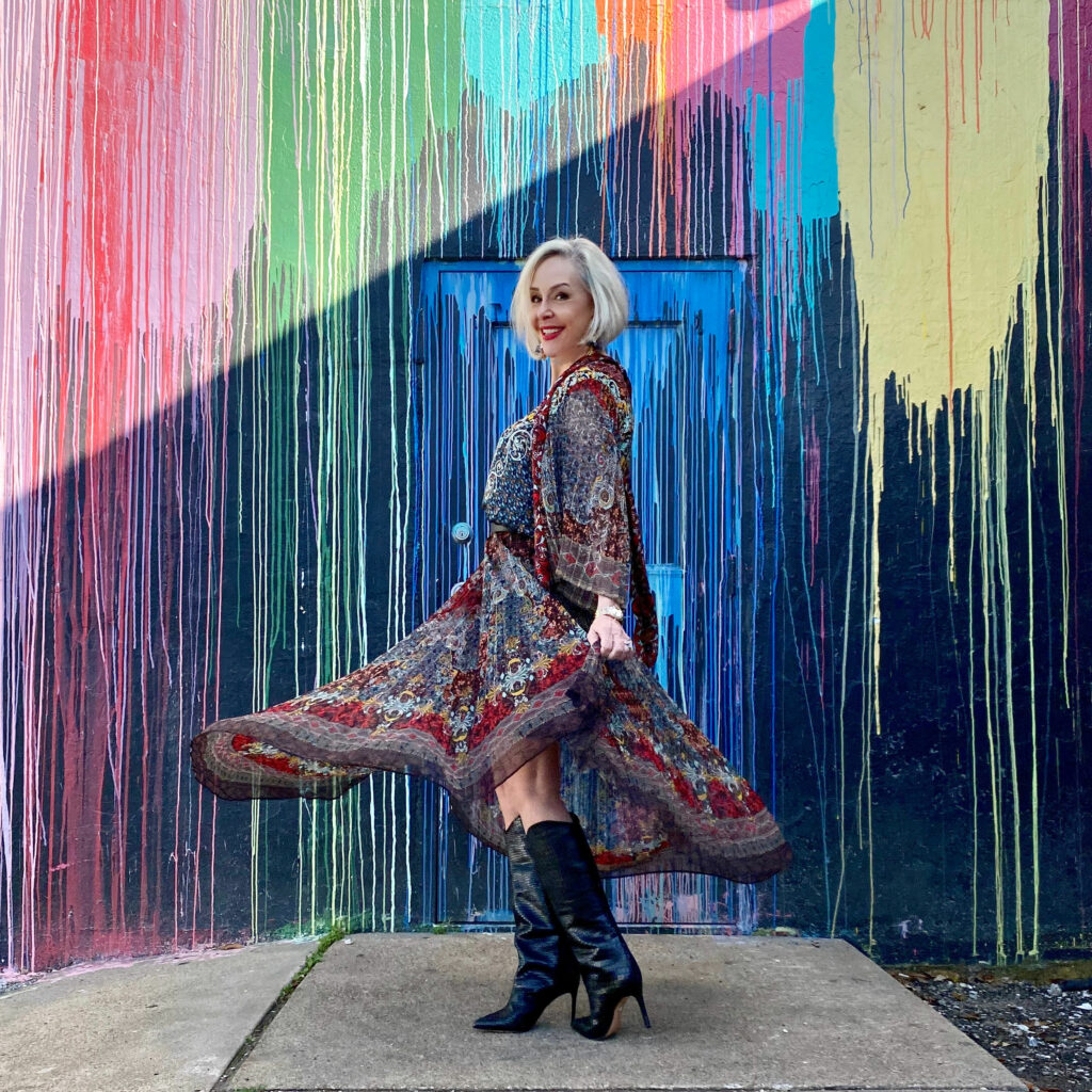 sheree Frede of the SheShe Show standing in front of paint drip mural wall wearing a flowy print skirt, knee boots