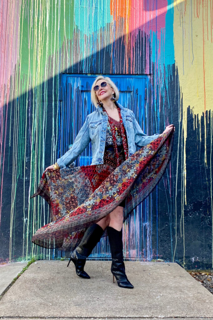 sheree Frede of the SheShe Show standing in front of paint drip mural wall wearing a flowy print skirt, knee boots and denim jacket