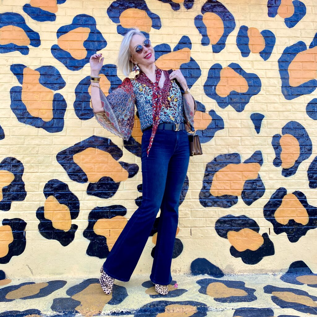 sheree Frede of the SheShe Show standing in front of paint drip mural wall wearing a flowy print bow blouse with flared jeans
