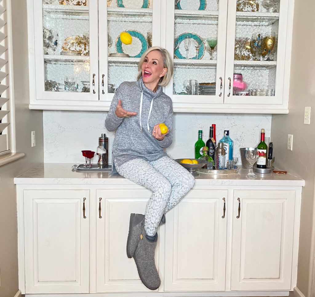 Sheree Frede of the SheShe Show wearing white print leggings with a gray sweatshirt sitting on counter top holding lemons