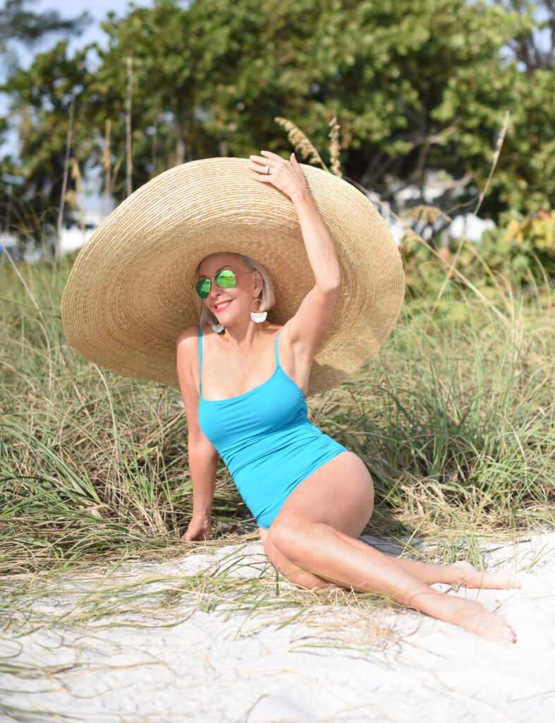Sheree Frede of the SheSheShow beach, turquoise one-piece swimsuit, very large straw hat, sunglasses