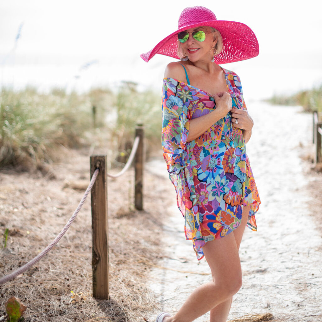 Sheree Frede of the SheSheShow multi colored print swimsuit coverup, kaftan, large hot pink hat, sunglasses, beach