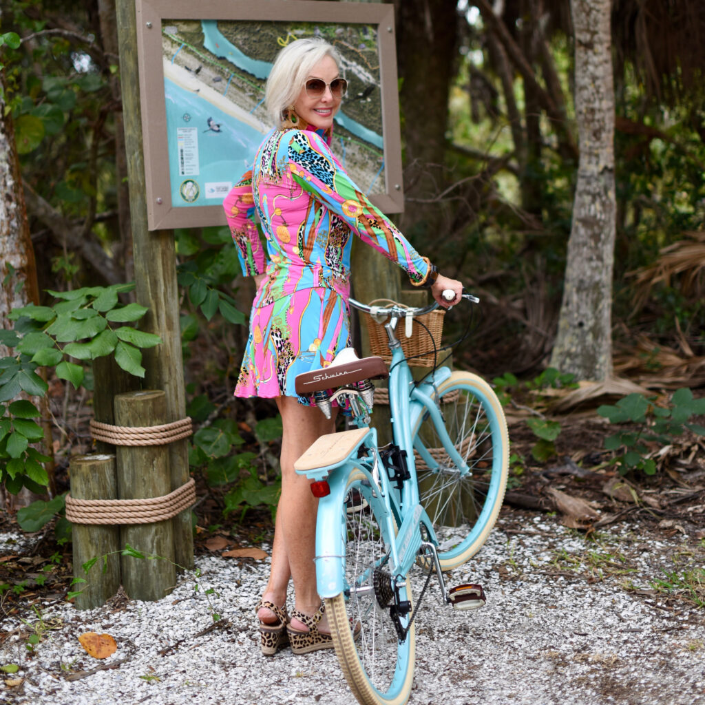 Sheree Frede of the SheSheShow multi-colored spf longsleeve top and skirt, big straw hat, island map by bike trail