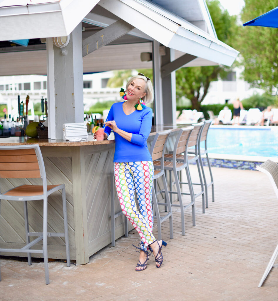 Sheree Frede of the SheSheShow sipping tropical drink, blue longsleeve top, white pants with multi-colored pattern,