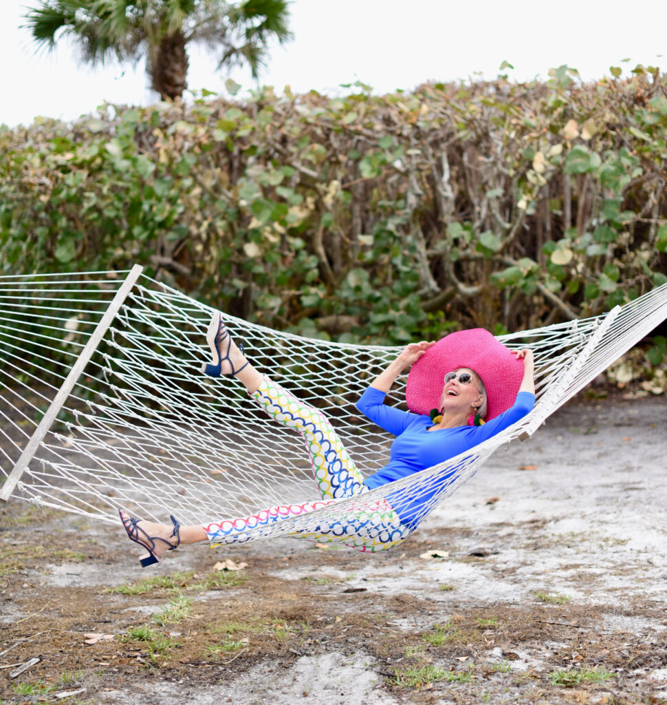 Sheree Frede of the SheSheShow, swinging in hammock blue longsleeve top, white pants with multi-colored pattern, large hot pink hat, denim blue sandals