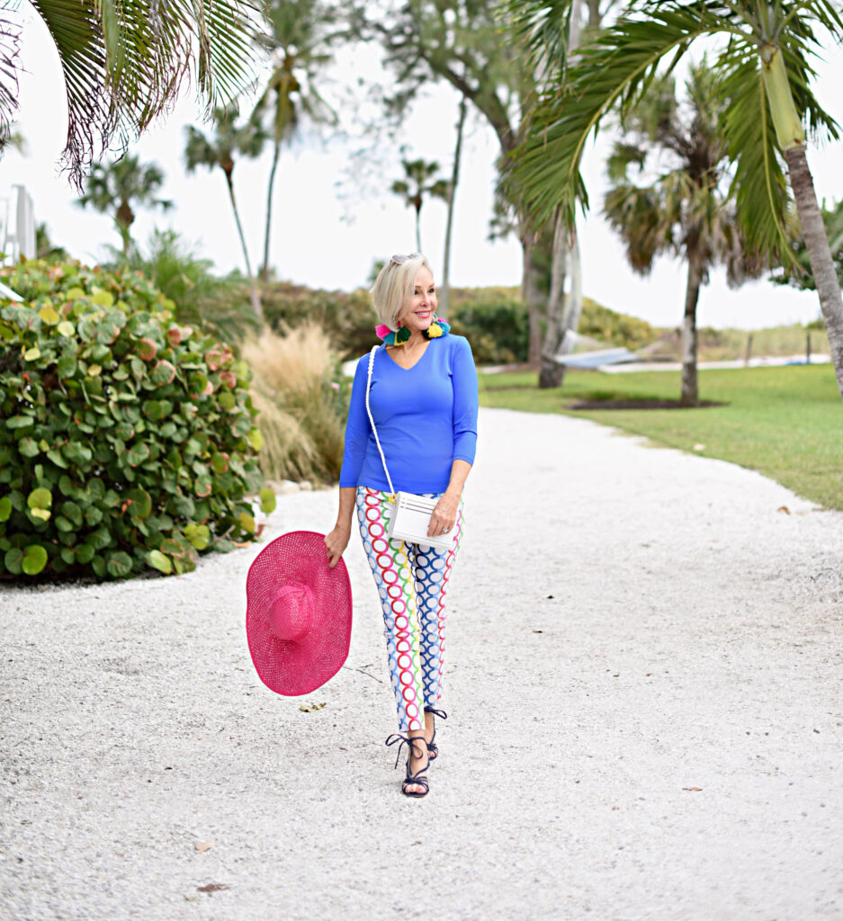 Sheree Frede of the SheSheShow blue long-sleeve top, white pants with multi-colored pattern, big pink hat, denim sandals