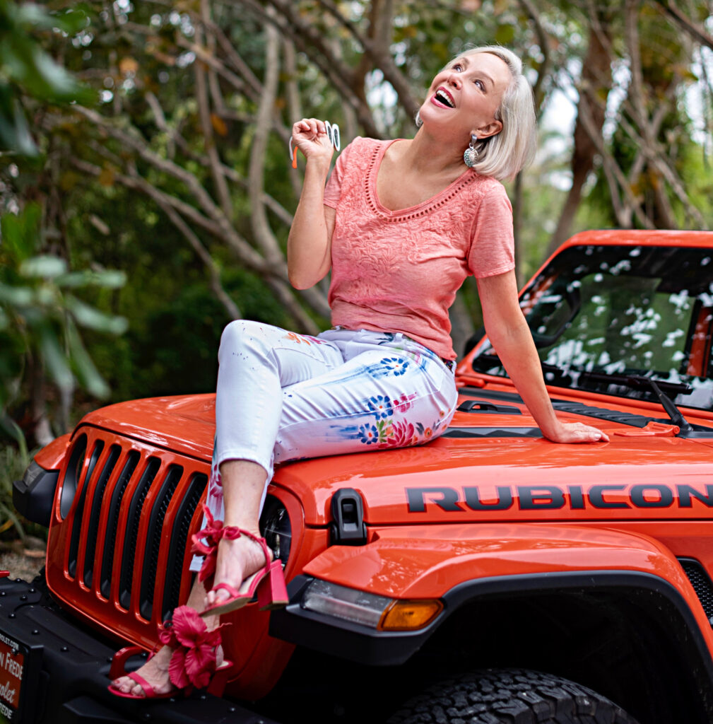 Sheree Frede of the SheSheShow orange jeep, resort, orange top, hand painted white jeans, pink hibiscus sandals