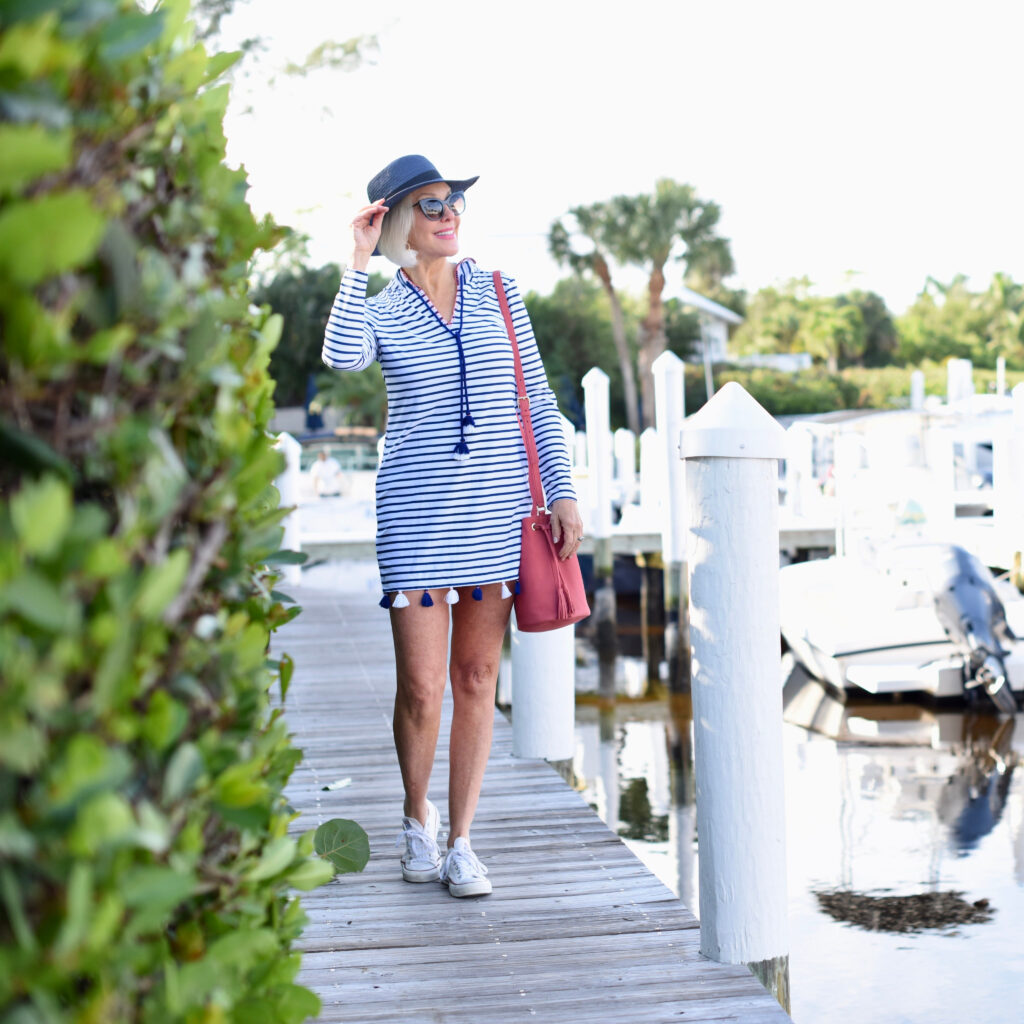 Sheree Frede of the SheSheShow at marina wearing a blue and white stripe dress with sneakers and navy boaters hat