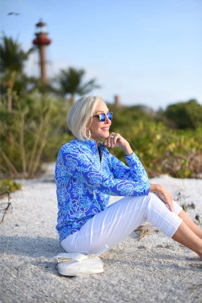 Sheree Frede of the SheSheShow white pants, long sleeve blue print zip front top, sunglasses, beach