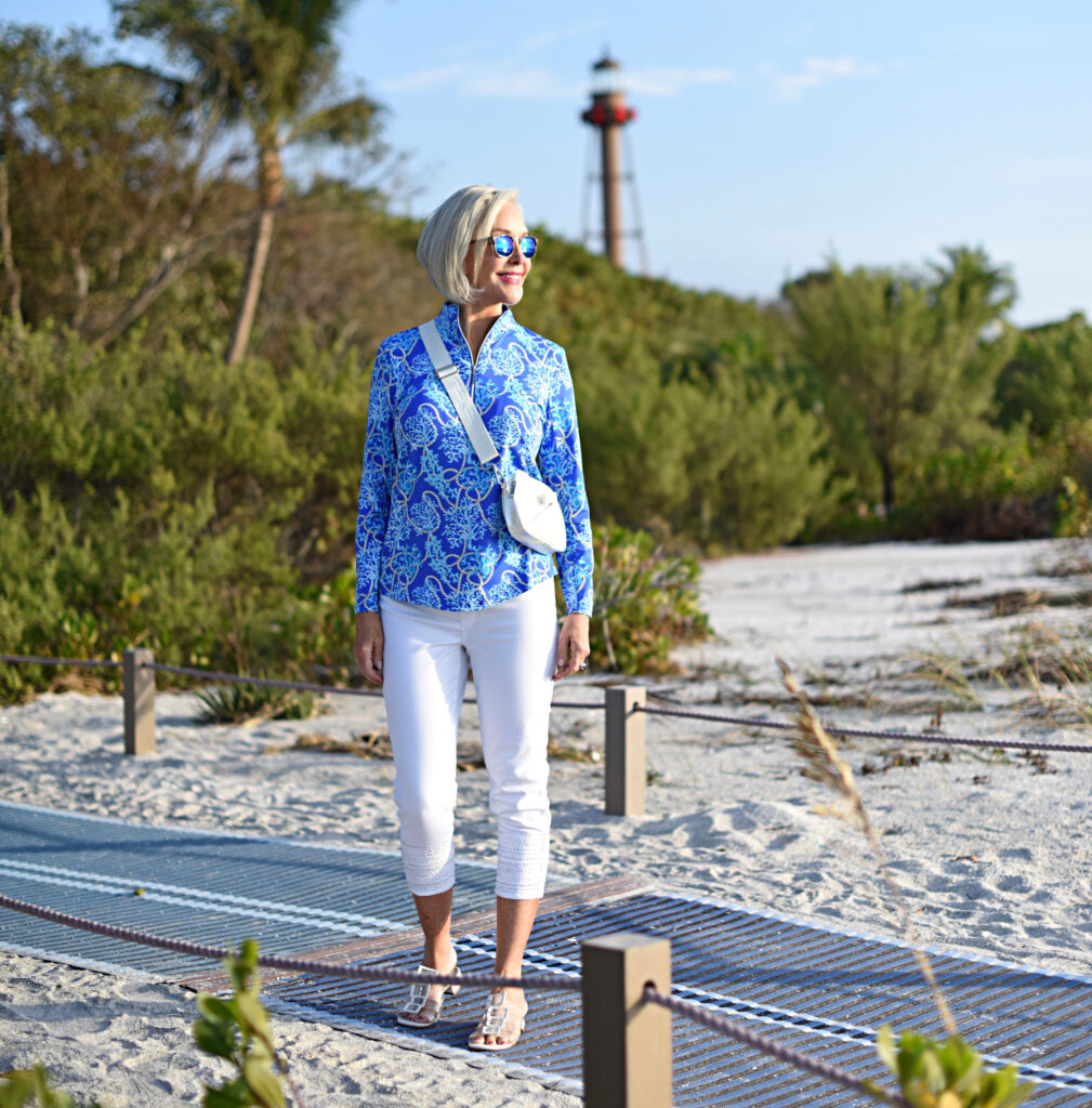Sheree Frede of the SheSheShow white pants, long sleeve blue print zip front top, sunglasses, beach, small white bag