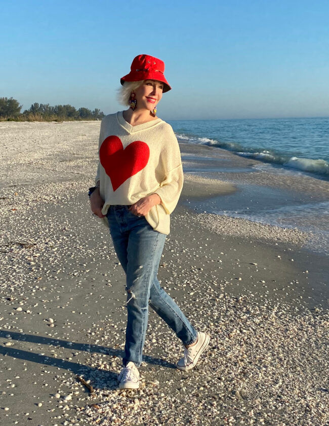 Sheree Frede of the SheShe Show walking on the brach wearing a cream sweater with a big red heart on the front with jeans and sneakers
