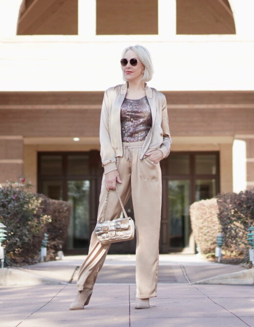 Sheree Frede of the SheShe Show wearing gold silk drawstring pants and bomber jacket with taupe suede booties