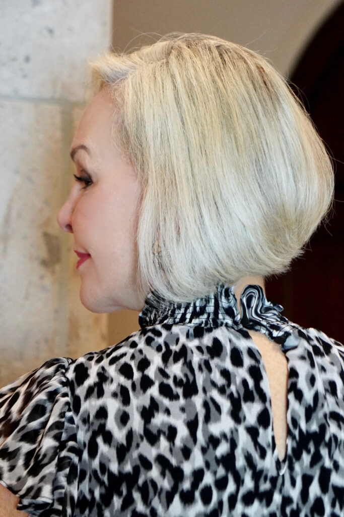 Sheree Frede of the SheShe Show standing by a stone column wearing a black and white leopard print top showing bob hairstyle