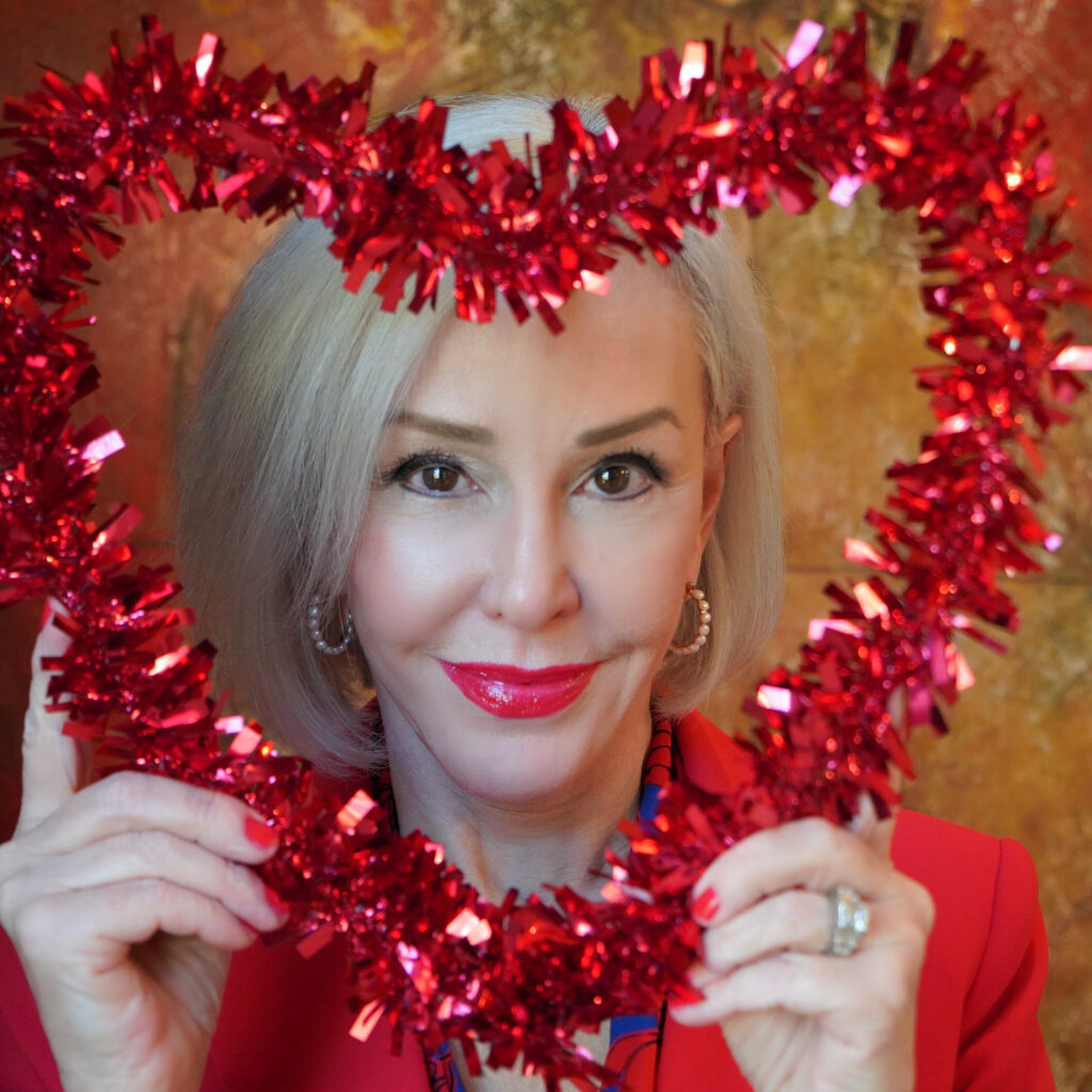 Sheree Frede of the SheShe Show holding a red heart wreath in front of her face