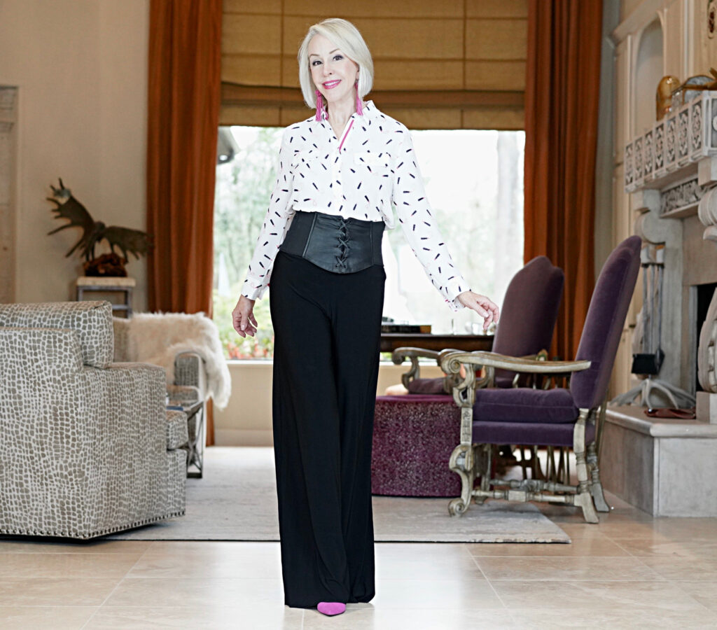 Sheree Frede of the SheShe Show standing in foyer wearing black pants and white print shirt