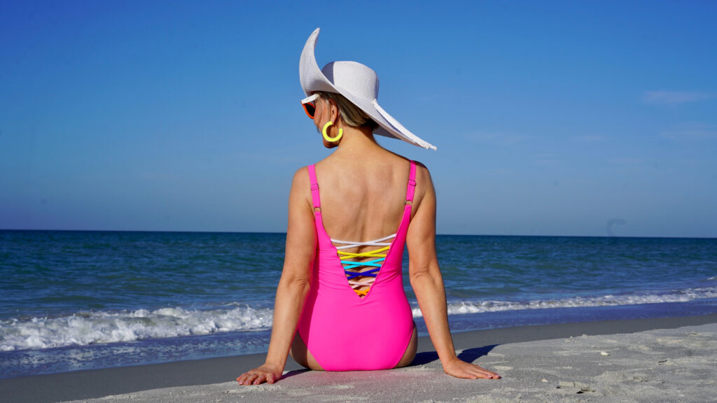 Sheree Frede of the SheShe Show in the water on the beach wearing a big hat and hot pink swimsuit