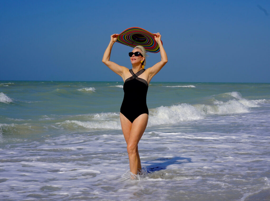 Sheree Frede of the SheShe Show in the water on the beach wearing a big hat and black one piece swimsuit