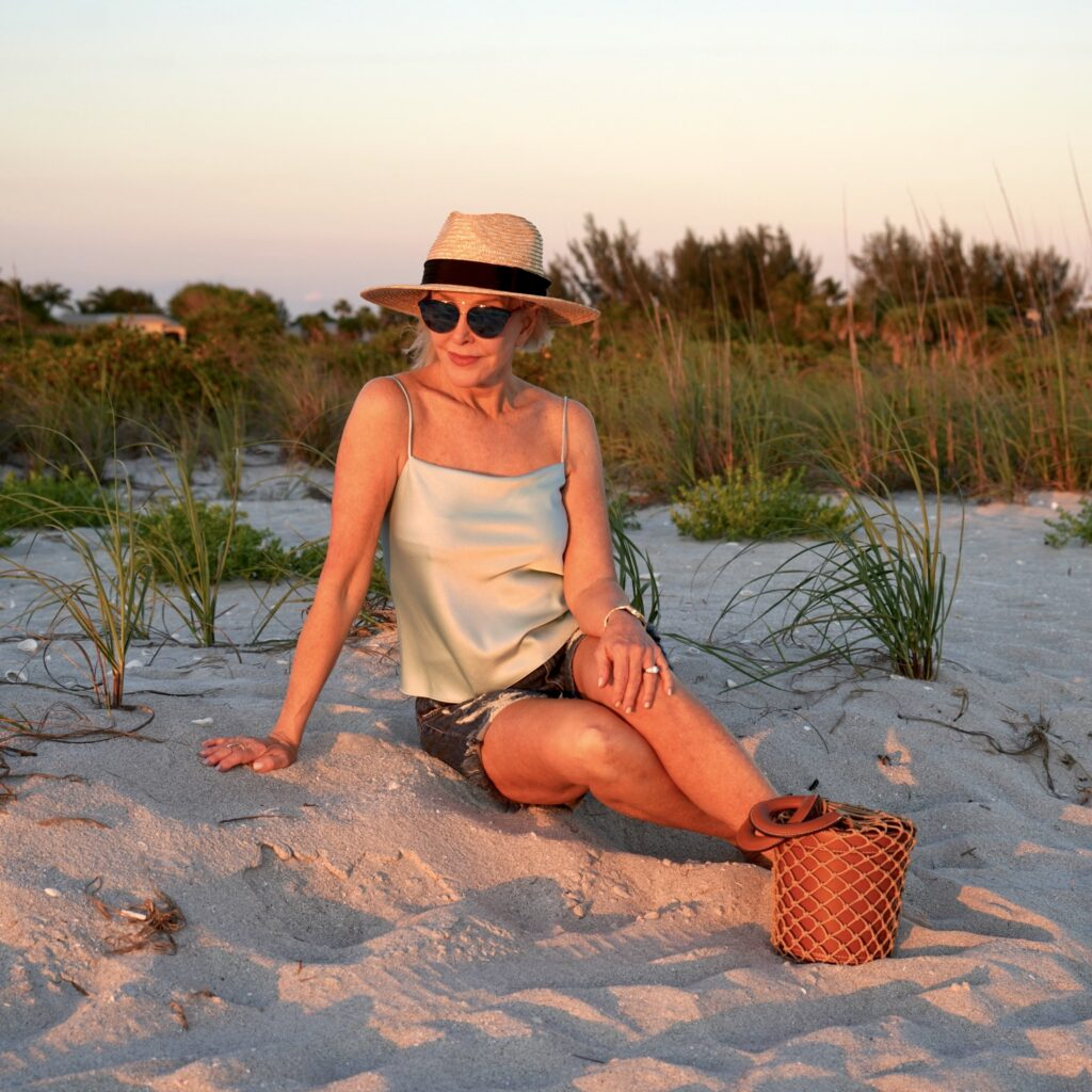 Sheree Frede of the SheShe Show Sitting on the beach wearing a Panama Hat