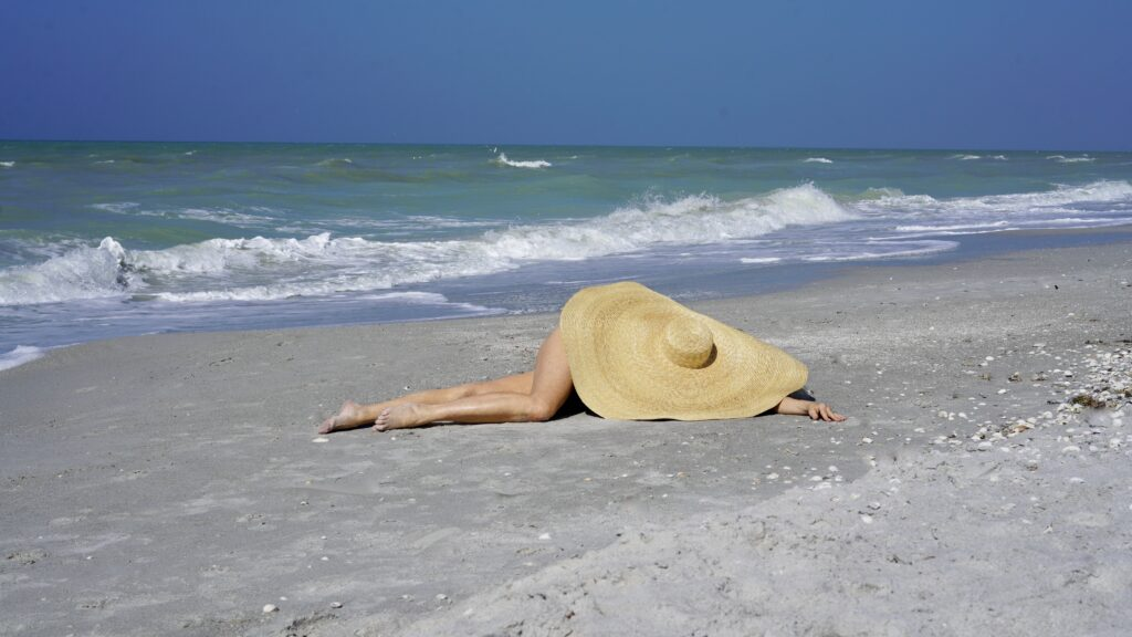 Sheree Frede of tSheree Frede of the SheShe Show laying down on the beach under a very large straw hat