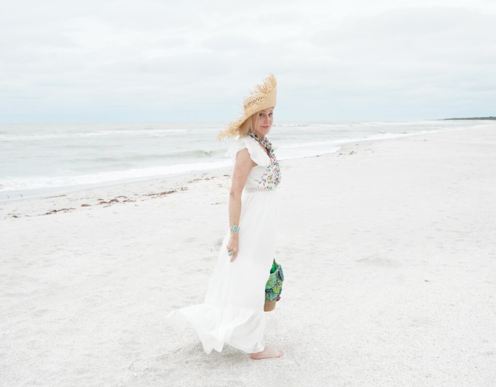 Sheree Frede of tSheree Frede of the SheShe Show walking on the beach weraring a long white dress and straw hat