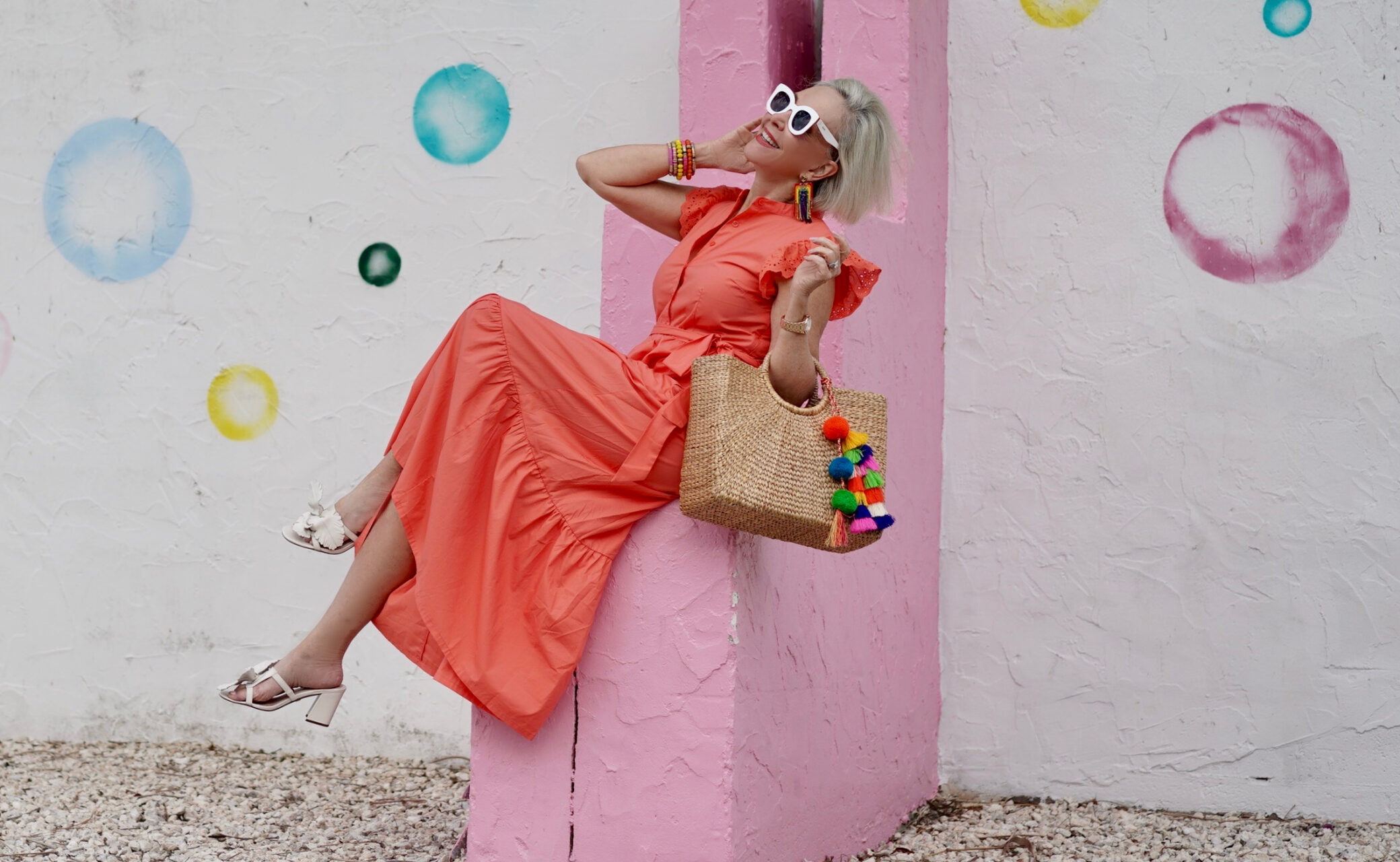 Sheree Frede of the SheShe Show stinnon on a pink and white wall wearing a bright orange maxi dress