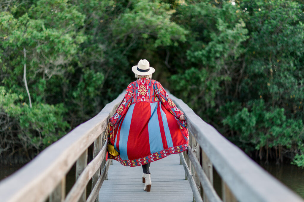 Sheree Frede of the SheShe Show walking on footbridge wearing a long duster and Panama Hat