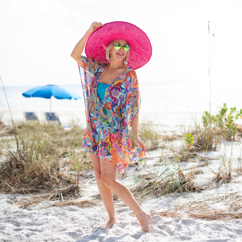 Sheree Frede of the SheShe SHow wearing a colorful swimsuit cover up and pink hat