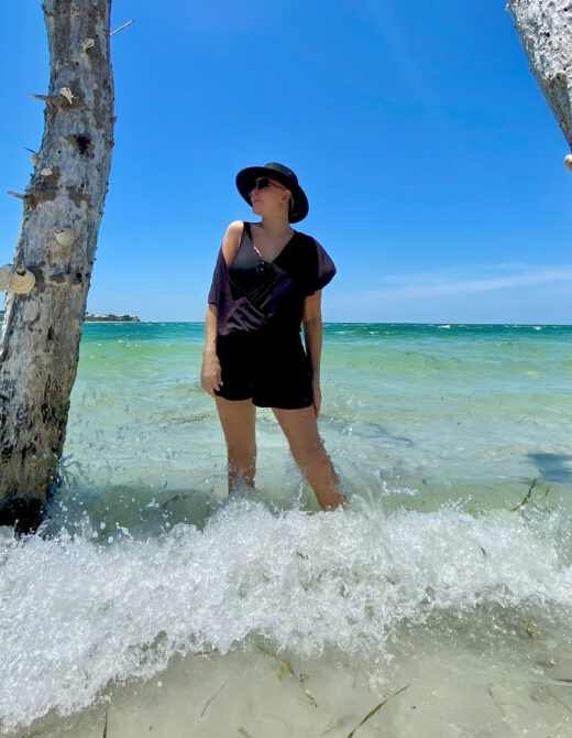 Sheree Frede of the SheShe SHow wearing a colorful swimsuit cover up and black hat