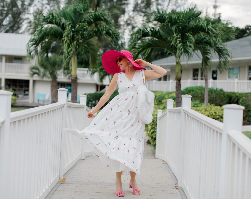 Sheree Frede of the SheShe Show walking on white bridge wearing a white maxi dress and hot pink hat