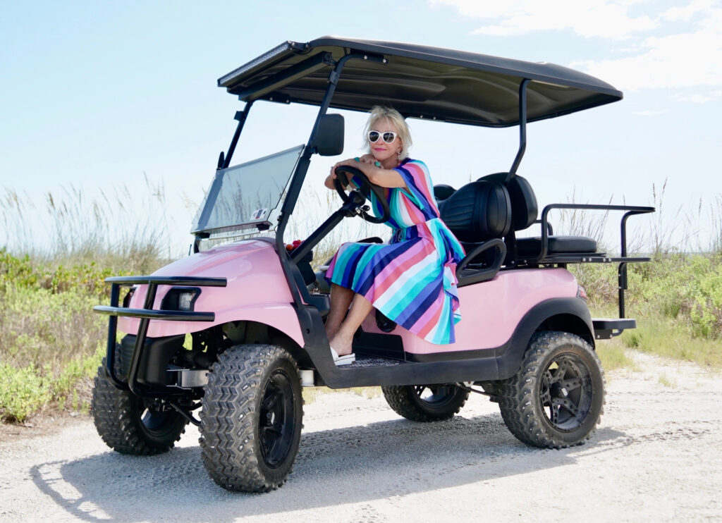 Sheree Frede of the SheShe Show wearing a multi color stripe midi dress with big white hat in pink golf cart