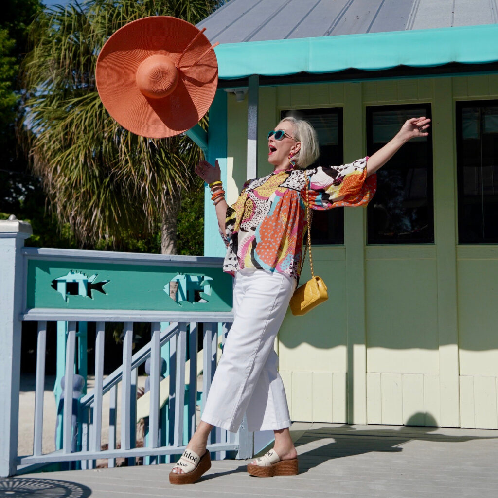 Sheree Frede of the SheShe Show wearing a multi color printed top and big orange hat